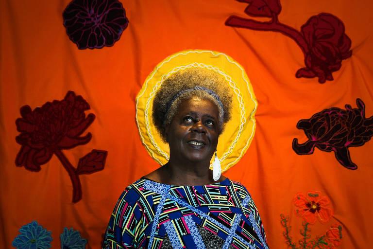 Com o olhar voltado para cima, mulher idosa posa para foto em frente a um painel estampado com flores e com o sol