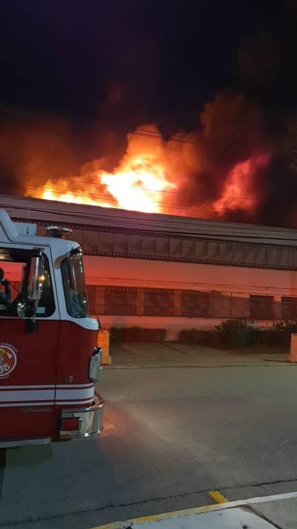 Caminhão de bombeiros em frente a uma instituição em chamas