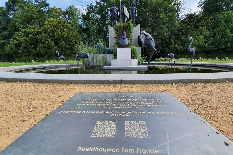 Placa em primeiro plano e, ao fundo, monumento em meio a um espelho d[água, com busto de homem barbudo sob 3 guerreiros africanos e em meio a cabeça de elefante, leão e pássaros africanos