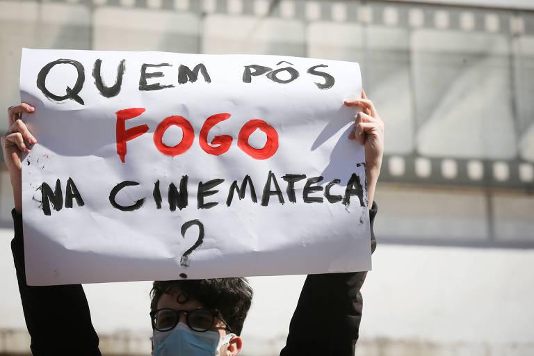 """Jovem segura cartaz, onde está escrito """"quem pôs fogo na cinemateca?"""""""