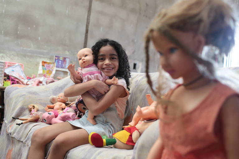 Manuela, 8, uma menina negra, segura uma boneca branca ao lado de outra, de tamanho real, que é loira e tem pele clara
