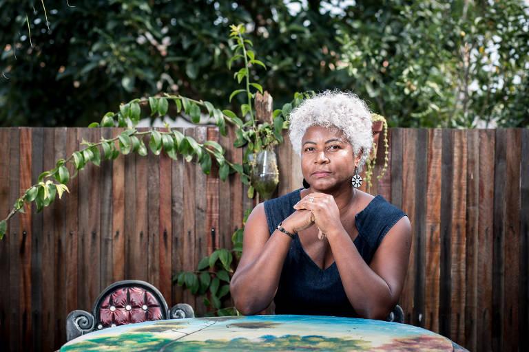 Viviane aparece sentada olhando para câmera. Ela apoia os braços sobre uma mesa. Ao fundo, um muro de madeira e árvores.