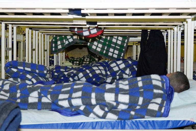 Moradores de rua dormem em camas de abrigo de Curitiba