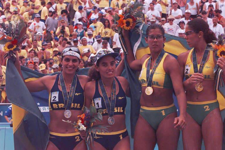Quatro mulheres de biquíni, uniforme do vôlei de praia, em pódio