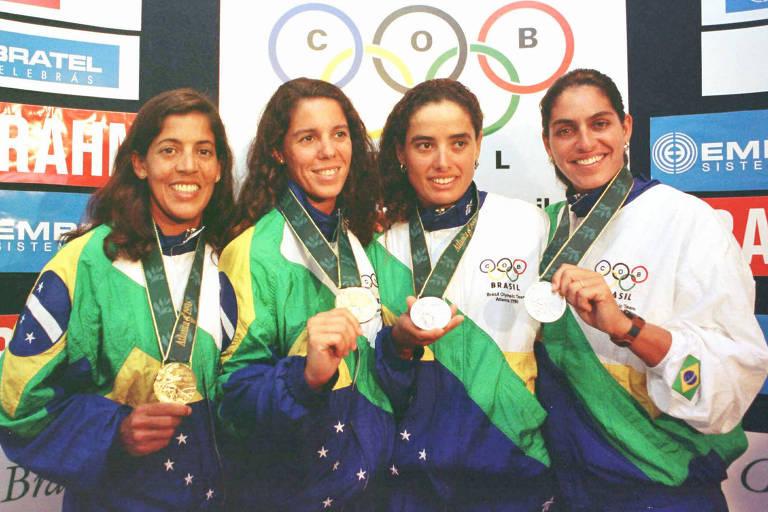 Jacqueline Silva, Sandra Pires, Adriana Samuel e Mônica Rodrigues em entrevista coletiva após a vitória nas Olimpíadas de Atlanta, em 1996; na foto, elas vestem o uniforme de pódio que não foi usado no pódio