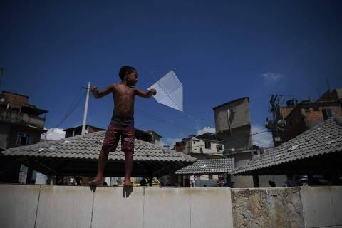 TOPSHOT - A boy flies a kite in the Mandela favela in Rio de Janeiro, Brazil, on April 3, 2021. (Photo by Carl DE SOUZA / AFP)