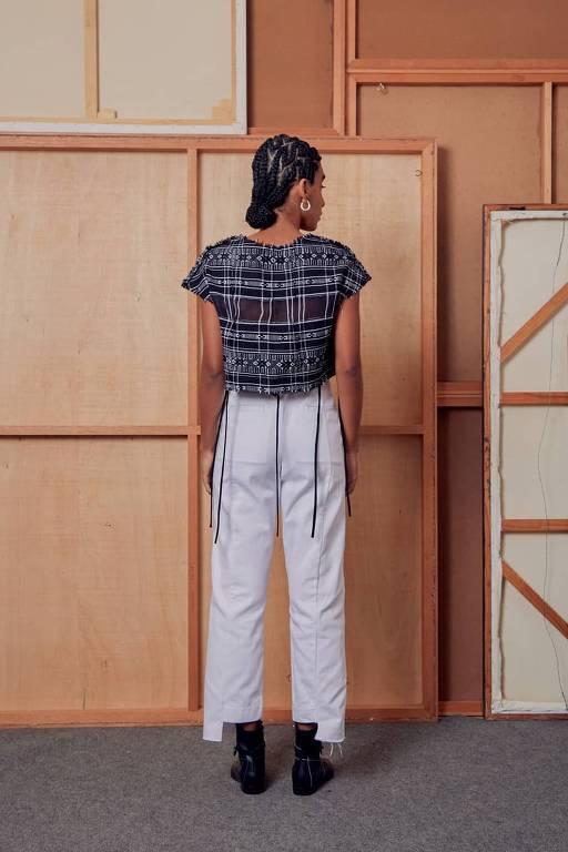 De costas, modelo posa com peças de Angela Brito
