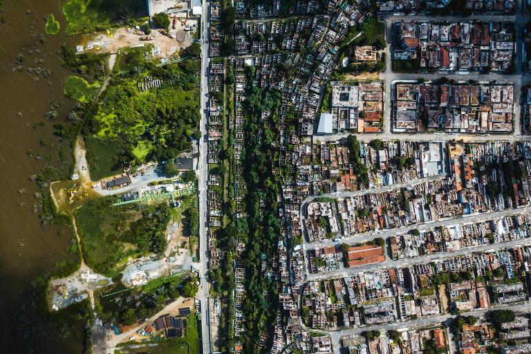 Vista aérea do Mutange e Pinheiro. Estruturas montadas pela empresa Braskem (à esq.) são vistas em contraste com diversas casas destelhadas nas áreas deixadas pelos moradores atingidos por rachaduras e tremores de terra
