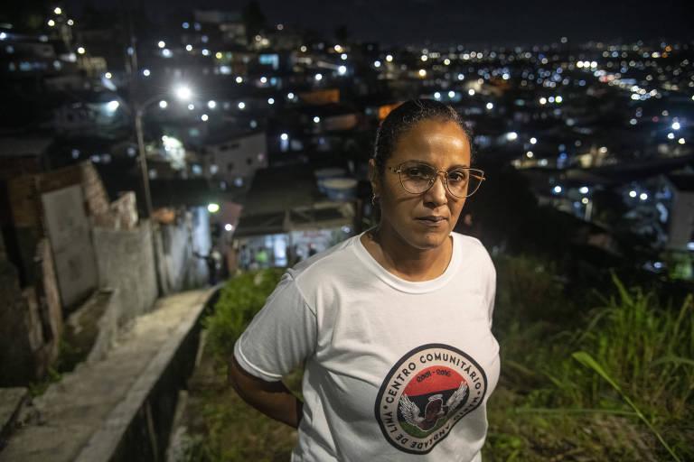 Joelma olha para a câmera com as mãos para trás das costas. Ao fundo, casas iluminam a noite no bairro do Ibura.