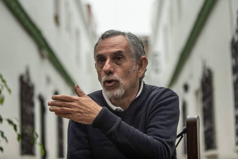 Pedro Francke, ao centro da imagem, de blusa azul, aponta para o lado direito enquanto fala