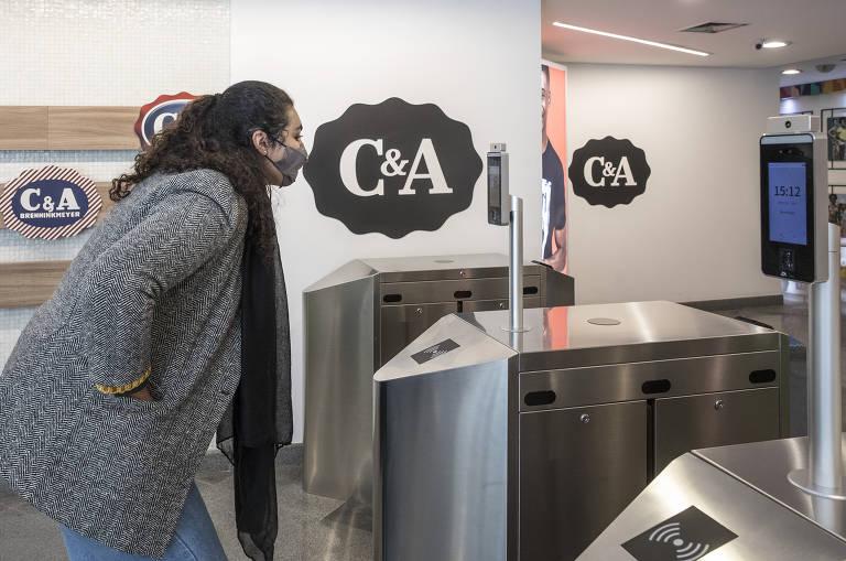 mulher mede temperatura e câmera identifica se ela está de máscara em aparelho acoplado à catraca que dá acesso ao escritório