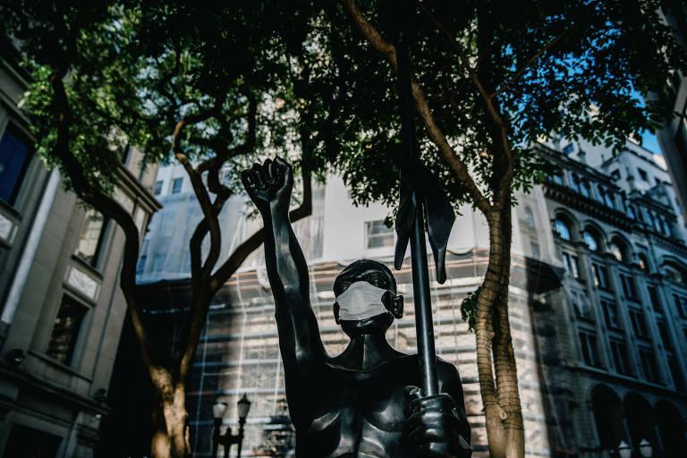 Estátua de Zumbi dos Palmares, na Praça Antônio Prado, no centro de São Paulo, recebe máscara durante a pandemia de Covid-19