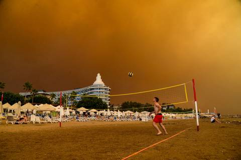 TOPSHOT - Dark smoke drifts over a hotel complex during a massive forest fire which engulfed a Mediterranean resort region on Turkey's southern coast near the town of Manavgat, on July 29, 2021. - At least three people were reported dead on July 29, 2021 and more than 100 injured as firefighters battled blazes engulfing a Mediterranean resort region on Turkey's southern coast. Officials also launched an investigation into suspicions that the fires that broke out Wednesday in four locations to the east of the tourist hotspot Antalya were the result of arson. (Photo by Ilyas AKENGIN / AFP)