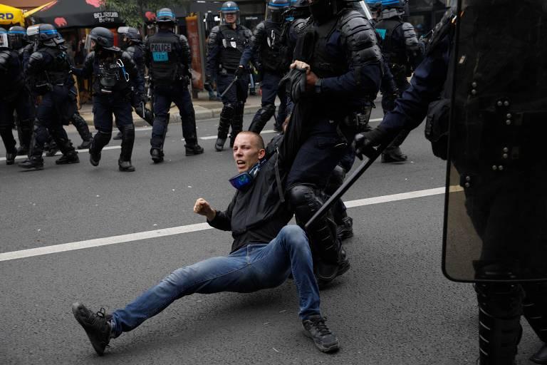 Manifestante é arrastado por policiais com barreira policial ao fundo