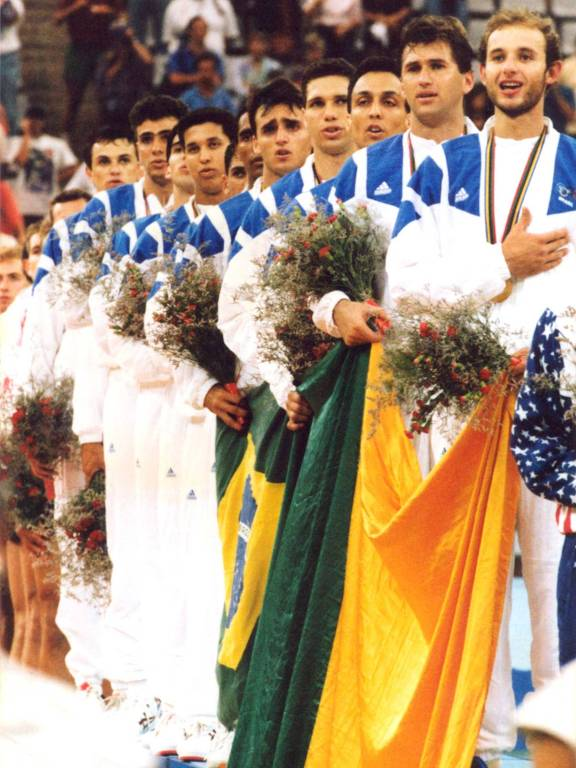 A seleção brasileira de vôlei masculino, no pódio, canta o hino nacional após receber a medalha de ouro