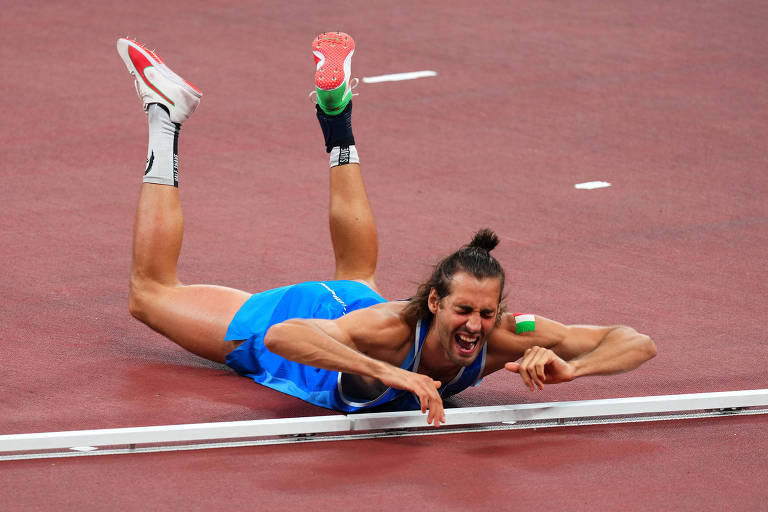 Gianmarco Tamberi se jogou no chão emocionado após a decisão de dividir a medalha de ouro no salto em altura