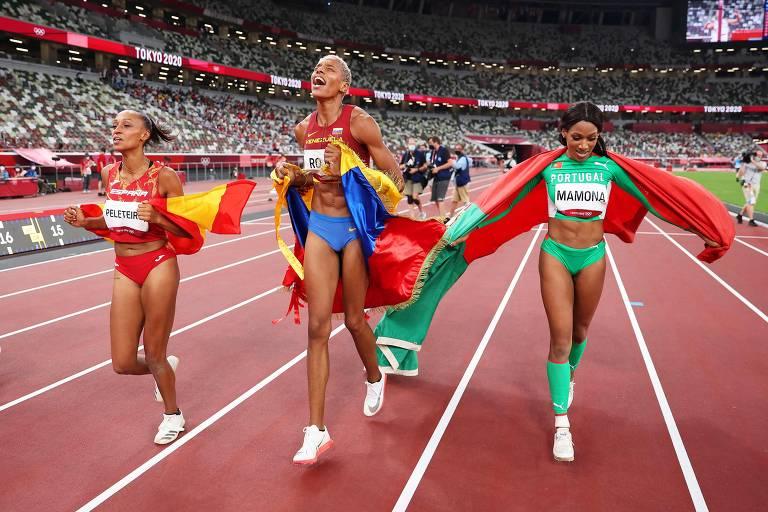 Atletas correm em estádio com as bandeiras de seus países nas costas