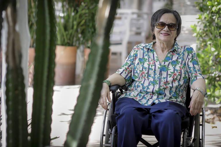 Maria da Penha, de camisa florida e calça azul, em sua cadeira de rodas, sorri para a câmera em um jardim, ao lado de plantas e cactos
