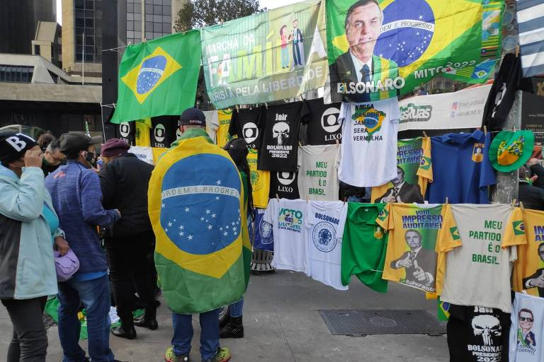 Varal pendurado entre postes na rua com camisetas com o rosto de Bolsonaro ou mensagens de apoio ao presidente