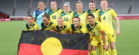 (From L, front) Australia's forward Hayley Raso, Australia's forward Kyah Simon, Australia's midfielder Tameka Yallop, Australia's forward Caitlin Foord, Australia's forward Sam Kerr and (From L, Rear) Australia's goalkeeper Lydia Williams, Australia's midfielder Emily van Egmond, Australia's defender Ellie Carpenter, Australia's midfielder Aivi Luik, Australia's defender Steph Catley and Australia's defender Clare Polkinghorne pose for a team photo with the Australian Aboriginal flag prior to the Tokyo 2020 Olympic Games women's group G first round football match between Australia and New Zealand at the Tokyo Stadium in Tokyo on July 21, 2021. (Photo by Yoshikazu TSUNO / AFP) ORG XMIT: jpAT55_202107210102