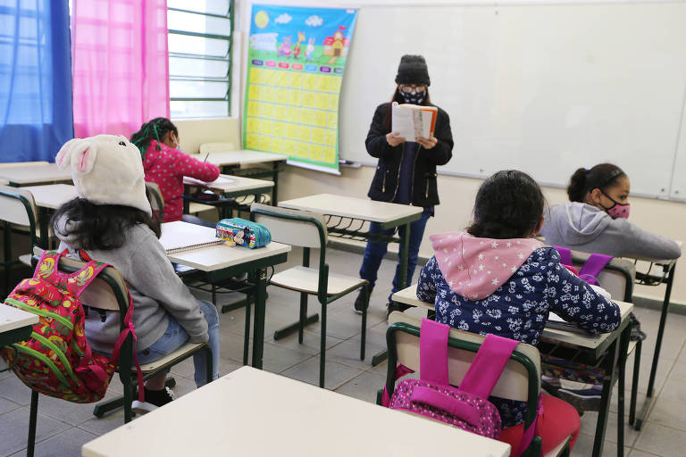 Foto mostra uma sala de aula com quatro crianças e uma professora na frente, em pé, lendo um livro.