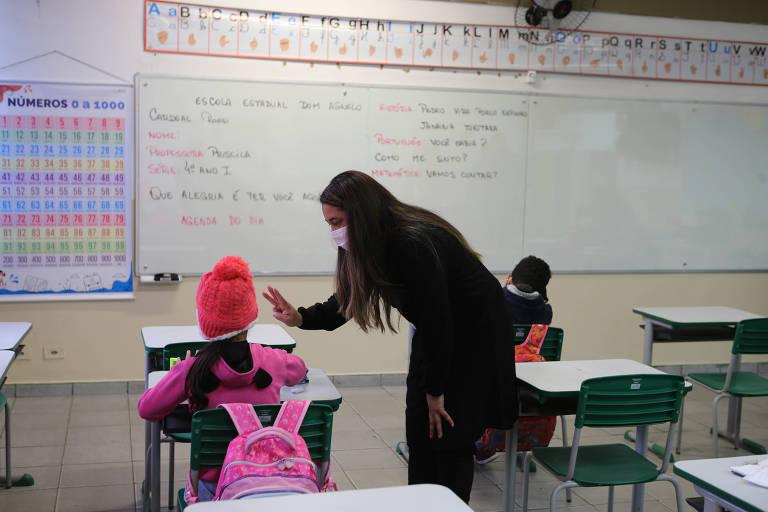 Em uma sala de aula, uma mulher com cabelo comprido, vestida de preto, de máscara, está curvada sobre uma aluna. A aluna, vestida de rosa e com uma touca, está de costas para a câmera.