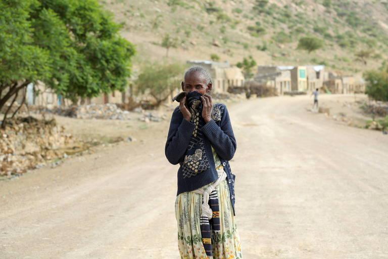 Mulher cobre o nariz e a boca para evitar o cheiro de cadáveres em sua vila no centro-sul de Tigré, na Etiópia