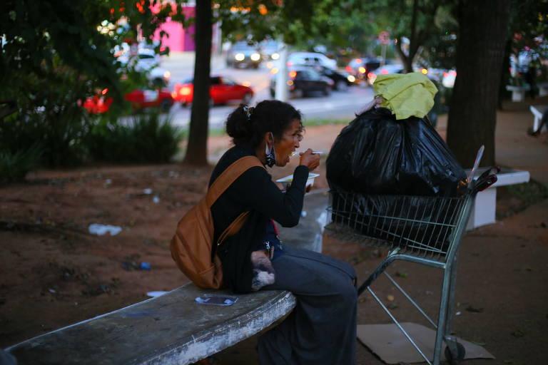 mulher come quentinha em banco de praça
