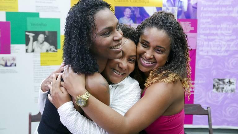 três mulheres negras se abrançando