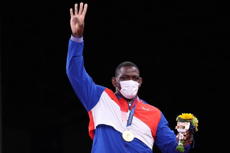 Atleta com máscara, medalha no pescoço e buquê de flores na mão faz o número quatro com a outra mão