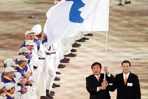 ORG XMIT: 154501_1.tif Jogos Olímpicos de Sydney (Austrália), 2000: representantes das Coreias do Sul e do Norte demonstram união e desfilam juntos na cerimônia de abertura da Olimpíada, o que não ocorria desde a Guerra da Coreia, em 1950, em Sydney (Austrália). Cerca de 10.300 atletas de 199 países começam a disputa dos 27º Jogos da era moderna. Serão 230 provas em 40 modalidades esportivas. Os Jogos Olímpicos de Sydney-2000 vão até o dia 1º de outubro (cerimônia de encerramento). *** Flag bearers Jang Choo Pak (L) of North Korea and Eun-Soon Chung of South Korea carry a special flag with the image of the Korean peninsula, at the head of their joint delegation during the opening ceremony of the 2000 Summer Olympics in Sydney 15 September 2000. North and South Korean delegations marched together for the first time at the Sydney games. AFP PHOTO/Jeff HAYNES