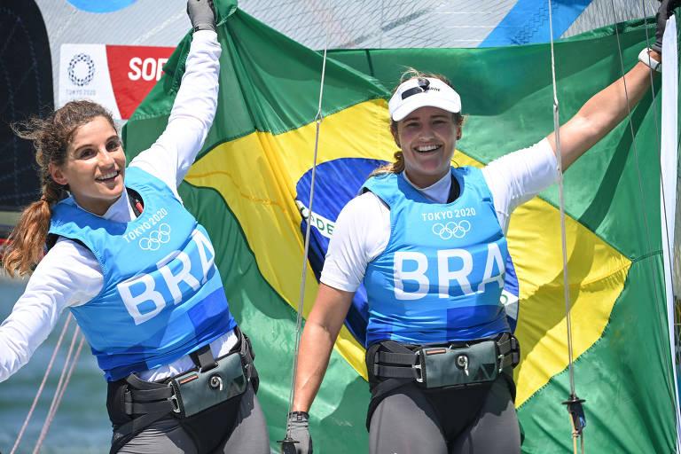 As bicampeãs olímpicas da vela Martine Grael e Kahena Kunze seguram a bandeira do Brasil