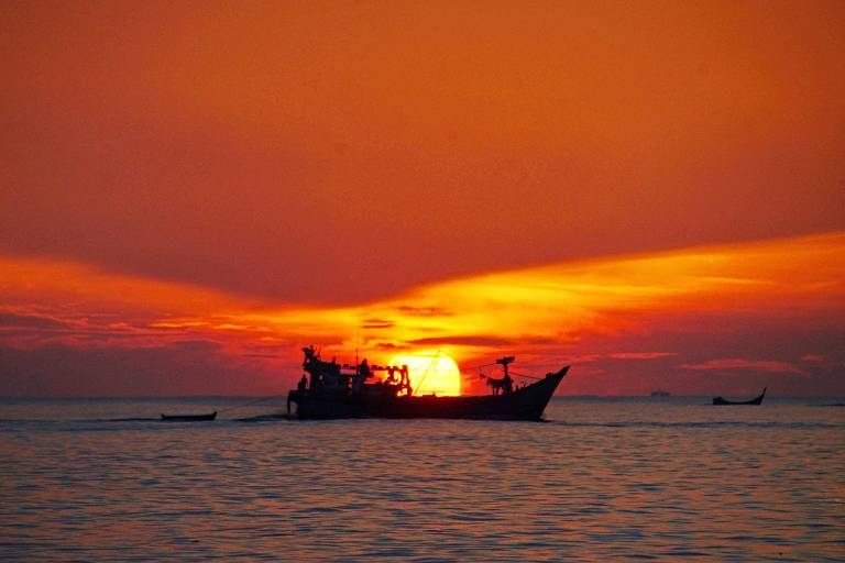 """Céu alaranjado do amanhecer, com sol no horizonte inclinado de forma a parecer estar """"a bordo"""" de barco pesqueiro"""