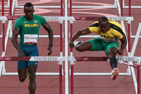 Brazil's Gabriel Constantino (L), Jamaica's Ronald Levy (C) and France's Wilhem Belocian (R) compete in the men's 110m hurdles heats during the Tokyo 2020 Olympic Games at the Olympic Stadium in Tokyo on August 3, 2021. (Photo by Giuseppe CACACE / AFP)