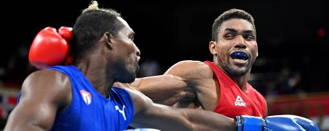 Brazil's Abner Teixeira (red) and Cuba's Julio La Cruz fight during their men's heavy (81-91kg) semi-final boxing match during the Tokyo 2020 Olympic Games at the Kokugikan Arena in Tokyo on August 3, 2021. (Photo by Luis ROBAYO / POOL / AFP)