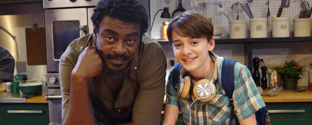 Homem negro de cabelo cacheado e escuro ao lado de um menino branco com cabelo castanho vestindo camiseta xadrez