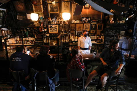 People sit at the bar at McSorley's Old Ale House as restrictions eased on indoor drinking in bars, allowing seating at the bar, during the outbreak of the coronavirus disease (COVID-19) in Manhattan, New York City, New York, U.S., May 3, 2021. REUTERS/Andrew Kelly ORG XMIT: PPP-AJK007