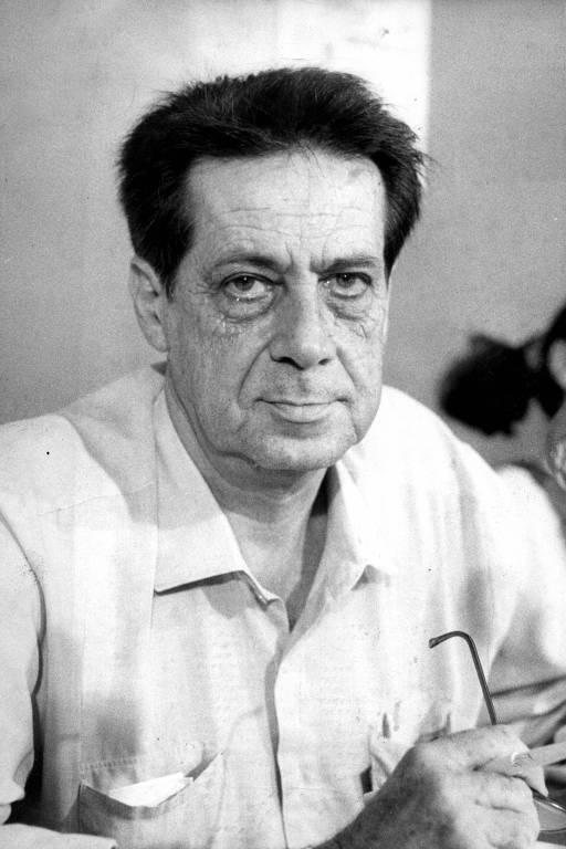 retrato em preto e branco de homem branco de cabelos pretos; ele veste camisa e não sorri para a foto