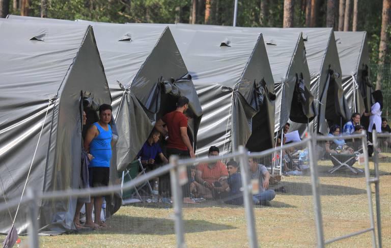 Homens em tendas parecidas com acampamento militar