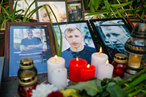 Candles are placed next to the portraits of Vitaly Shishov, a Belarusian activist living in exile who was found hanged in a park near his home this morning, during a commemoration rally next to the Belarusian Embassy to Ukraine in Kyiv, Ukraine August 3, 2021. REUTERS/Gleb Garanich ORG XMIT: PPP-GAR06