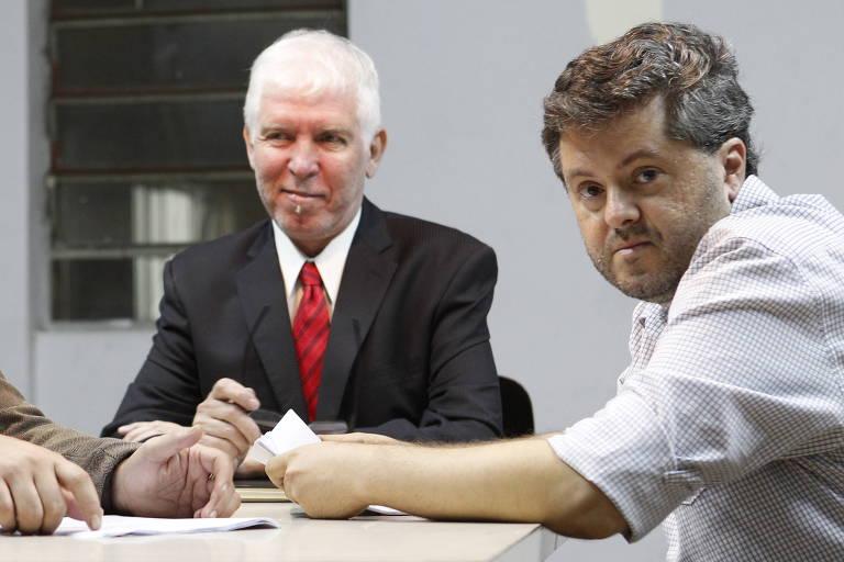 homem branco de cabelo castanho claro e barba rala usando camisa com a manga erguida à esquerda, sentado e, do outro lado da mesa, homem branco de cabelo e cavanhaque brancos usando terno preto e gravata vermelha