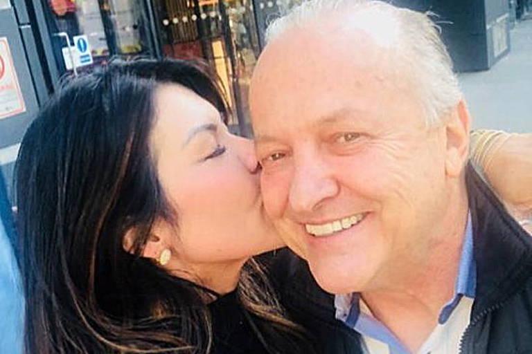 Mulher beija homem no rosto em selfie
