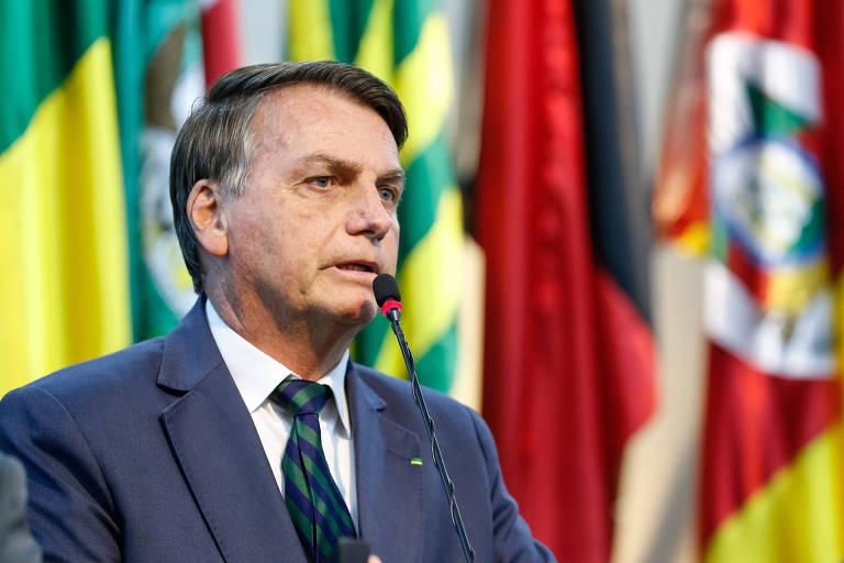 Jair Bolsonaro fala ao microfone; ao fundo, há diferentes bandeiras