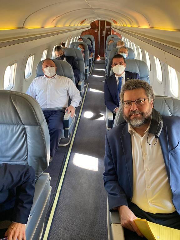 Ernesto Araújo (à frente), Eduardo Pazuello (esq.) e o deputado Luis Miranda (gravata azul) durante voo