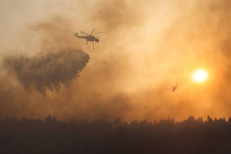 Helicóptero solta água ao voar sobre chamas