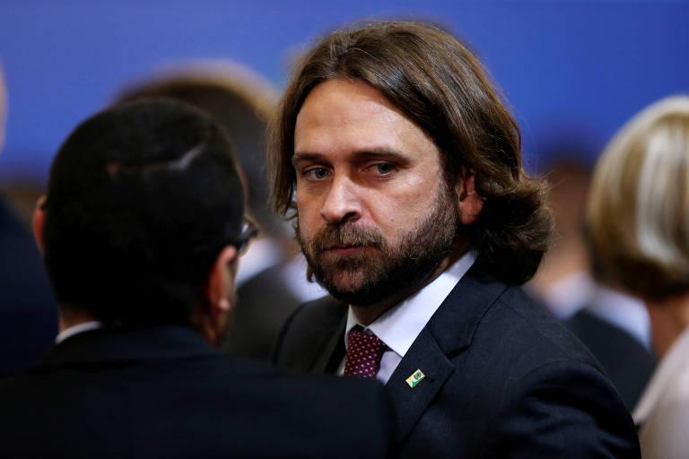 Santine, um homem com cabelo comprido, barba usando terno, olha para o lado enquanto conversa com outro homem, que aparece de costas