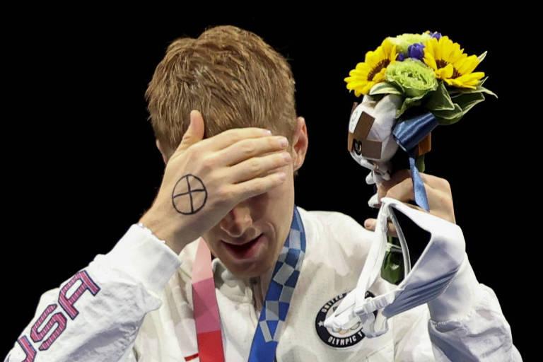 O esgrimista americano Race Imboden sobe ao pódio com 'X' desenhado na mão em forma de protesto