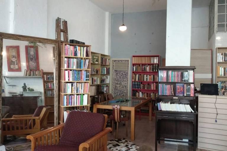 foto de um espaço com estantes de livros de madeira, espelho e poltrona