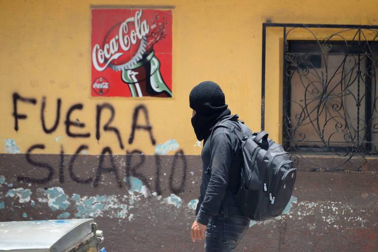 Integrante de milícia indígena formada para combater o crime organizado passa em frente a pichação que pede a saída de matadores na cidade de Pantelho, no estado de Chiapas, no México