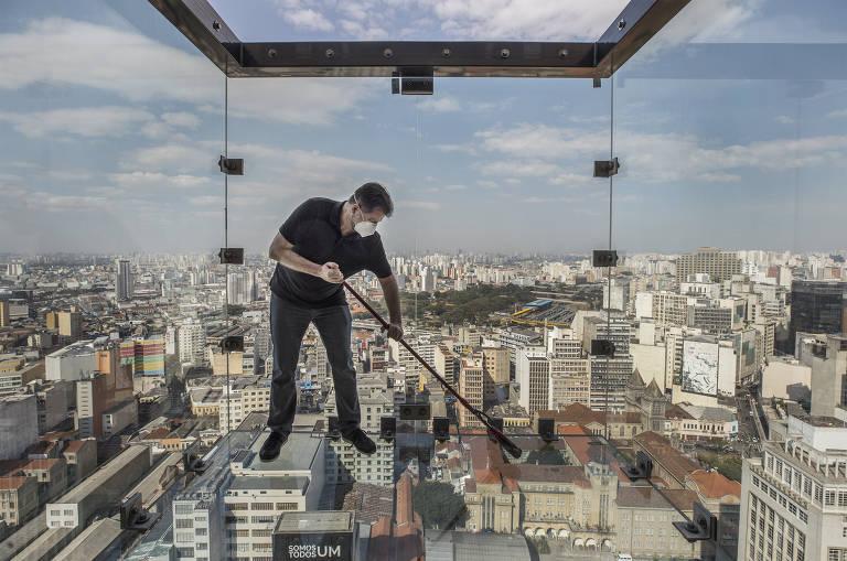 Alessandro Matineli, um dos sócios do Sampa Sky, limpa vidro do deque